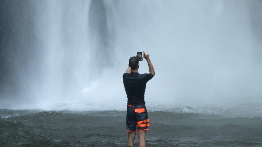 čovek slika telefonom u vodopadu