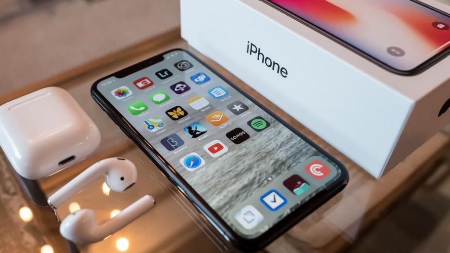 Iphone telefon na stolu pored koga se nalazi njegova kutija i bele slušalice