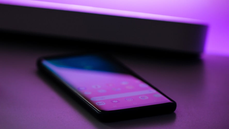 Žljubičasta svetla koja se prelamaju preko touch telefona