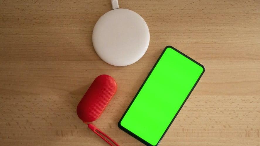 Telefon pored bežičnog punjača na stolu