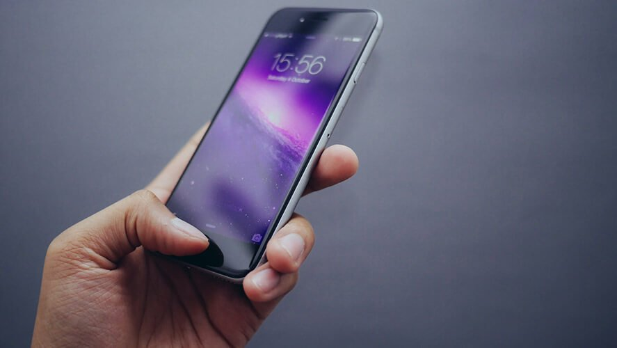 Crni pametni mobilni telefon u ruci na sivoj pozadini