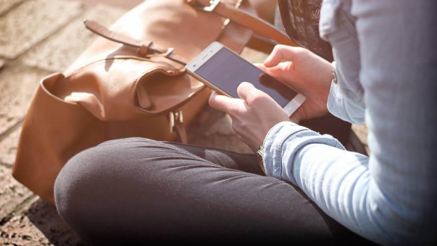 Devojka koja drži mobilni telefon u ruci