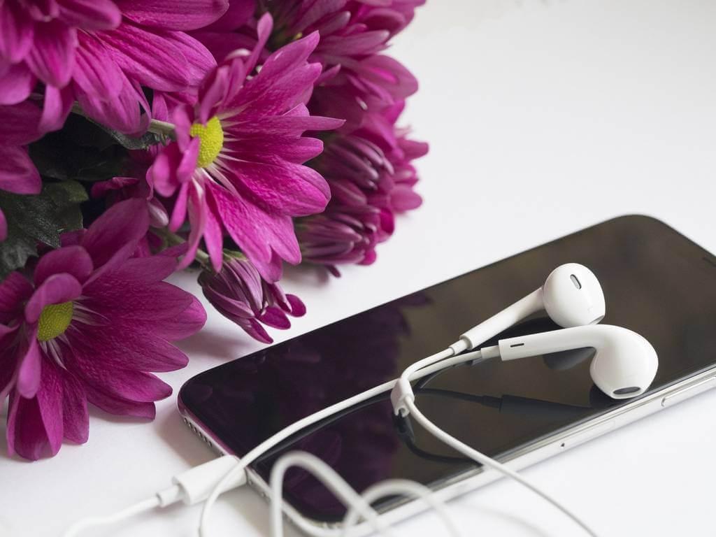 crni telefon i bele earphones slušalice pored ljubičastog buketa cveća