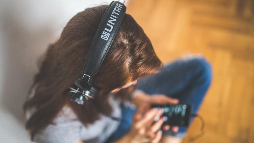 devojka sa slušalicama sedi na podu