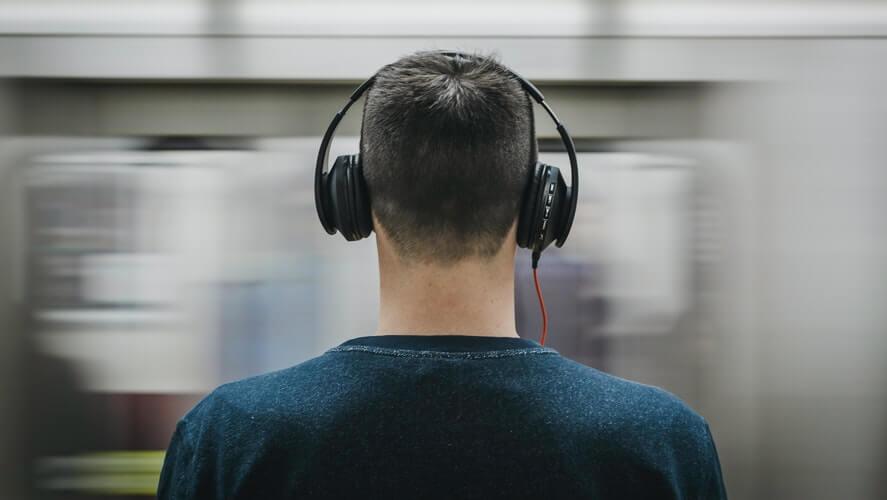 muškarac sa slušalicama na železničkoj stanici